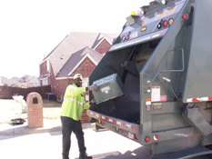 Trash man dumping recycling in trash truck